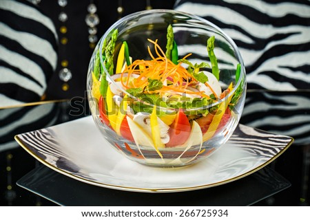 Fresh vegetable salad served in the big glass bowl - stock photo