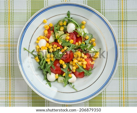 fresh vegetable salad with corn, tomato, arugula and mozzarella cheese - stock photo