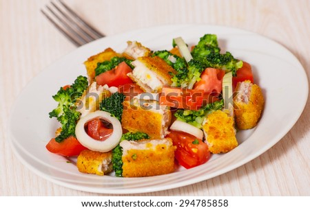 Fresh vegetable salad with fried breaded fish fillets - stock photo