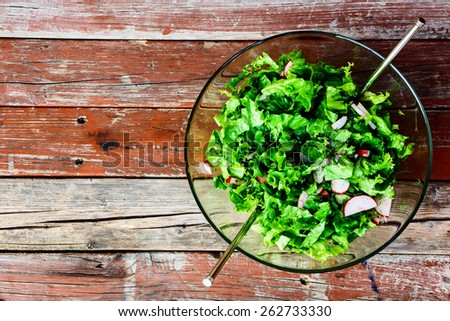 Fresh vegetable salad with lettuce and radishes on rustic wooden background. Healthy or vegetarian eating concept. Top view. - stock photo