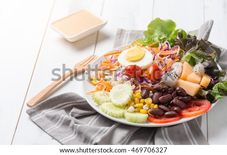 fresh vegetable salad with mix fruits on white wood background