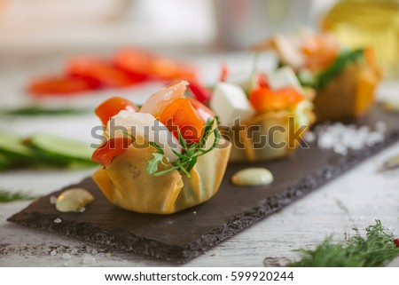 Fresh vegetable salad with shrimps and feta cheese on a white plate on a wooden table