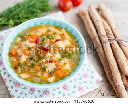 Fresh vegetable soup made of carrot, potato, red bell pepper, tomato, celery in bowl with parsley and grissini in the back. Selective focus - stock photo