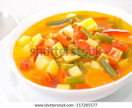 Fresh vegetable soup made of green bean, carrot, potato, red bell pepper, tomato in bowl