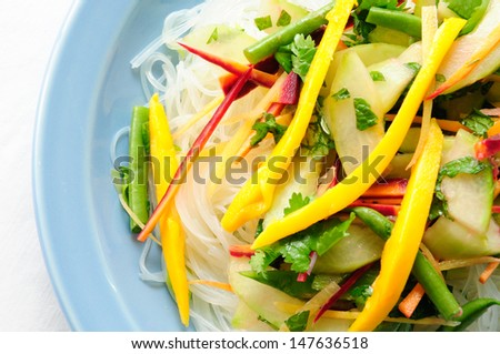fresh vegetable stir fry with sliced mango over glass noodles - stock photo