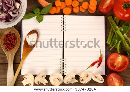 Fresh vegetables and blank recipe book - stock photo