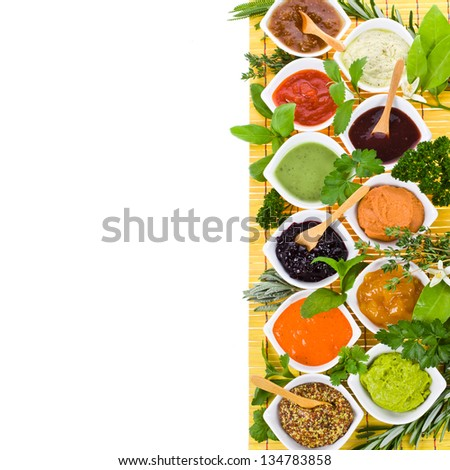 fresh vegetables and herbs and cooking sauces in white bowls on a yellow mat  isolated on a white background   with sample text - stock photo