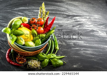 Fresh vegetables and herbs in a bowl on a black background - stock photo