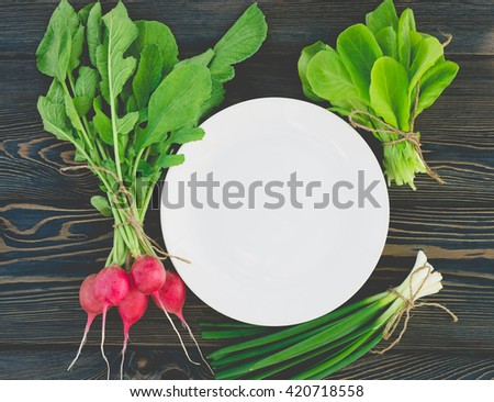 fresh vegetables and herbs on a plate cooking raw ingredients on kitchen - stock photo