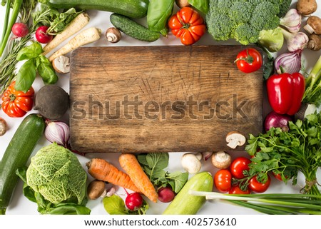 fresh vegetables and ingredients for cooking around vintage cutting board on white background
