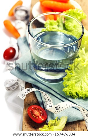 Fresh vegetables and measurement tape - diet and healthy eating concept - over white - stock photo