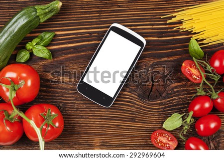 Fresh vegetables and pasta on wooden table with smartphone and empty white screen.  - stock photo