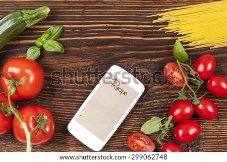 Fresh vegetables and pasta on wooden table with smartphone and recipe on screen.