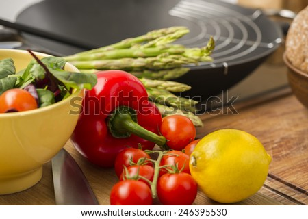 Fresh vegetables and salad ingredients on a wooden counter in a kitchen with cherry tomatoes, lemon, asparagus, red bell pepper and leafy herbs - stock photo