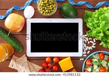 Fresh vegetables and tablet on wooden table, top view - stock photo