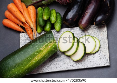 Fresh vegetables are laid out on the kitchen plank on the table.
