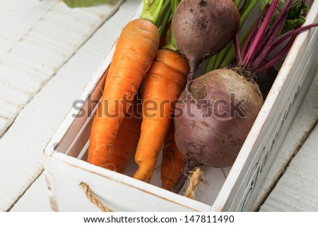 Fresh vegetables  carrots, beetroots in white wooden box on table. Selective focus. Rustic style.