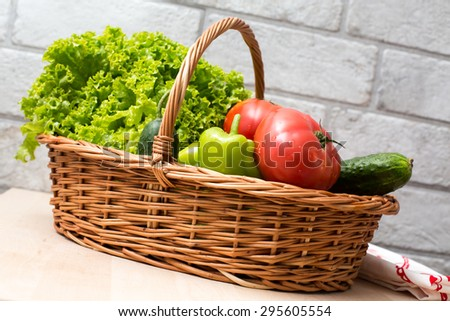 Fresh vegetables covered with water drops in basket. Organic Tomatoes, cucumber, pepper and vibrant green lettuce from the market. Fresh raw food.