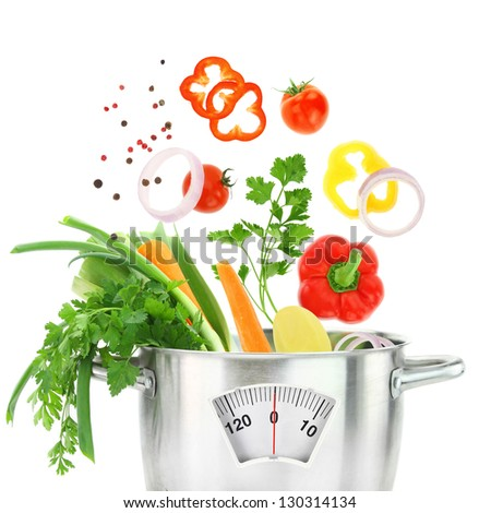 Fresh vegetables falling into a casserole pot with weight scale - stock photo