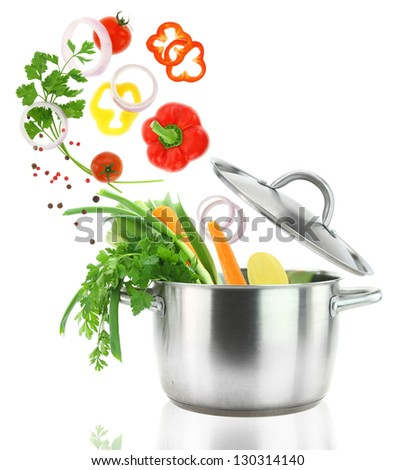 Fresh vegetables falling into a stainless steel casserole pot - stock photo