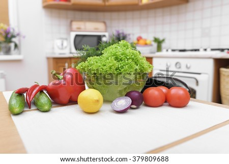 Fresh vegetables for salad on a kitchen table. - stock photo