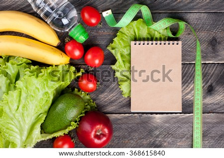 Fresh vegetables, fruits and measuring tape. Healthy food and healthy lifestyle concept. Open blank notebook, pen, lettuce, avocado, apple, banana, water bottle on wooden table. Top view - stock photo
