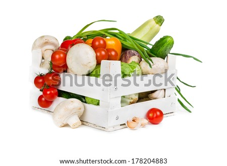 Fresh vegetables in a wooden box isolated on white background