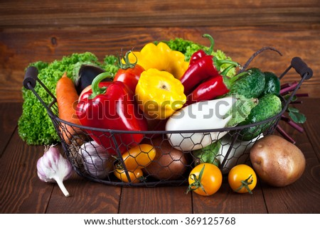 Fresh vegetables in basket on wooden board healthy eating - stock photo