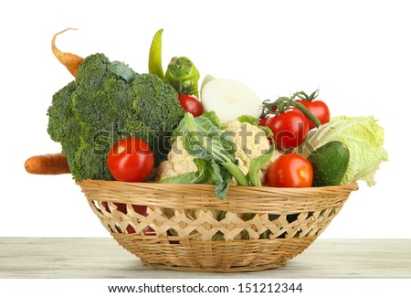 Fresh vegetables in basket on wooden table on white background