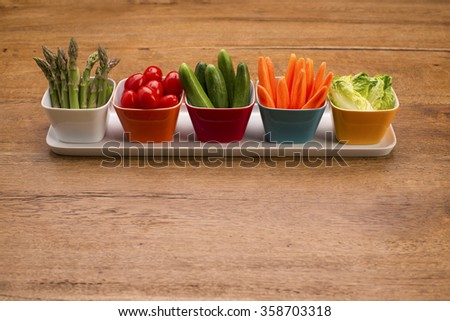 Fresh vegetables in colorful bowls on a wooden table. Party food. Asparagus, cucumbers, carrots, lettuce leaves and cherry tomatoes.  - stock photo