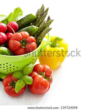 Fresh vegetables in green colander with water drops - stock photo