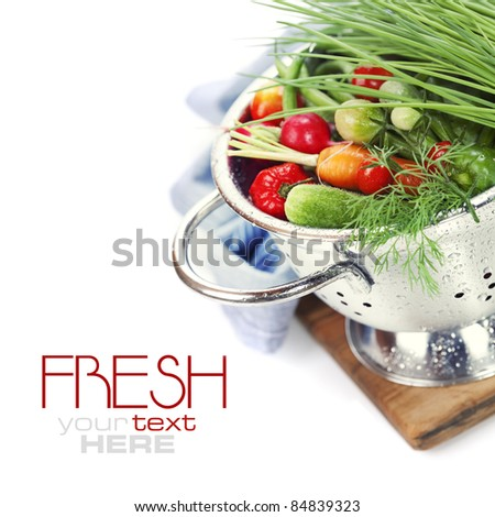 Fresh vegetables in metal colander over white (with sample text) - stock photo