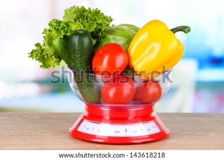 Fresh vegetables in scales on table in kitchen - stock photo