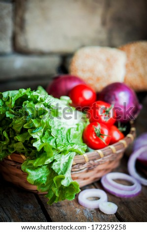 Fresh vegetables in the basket on wooden background - stock photo
