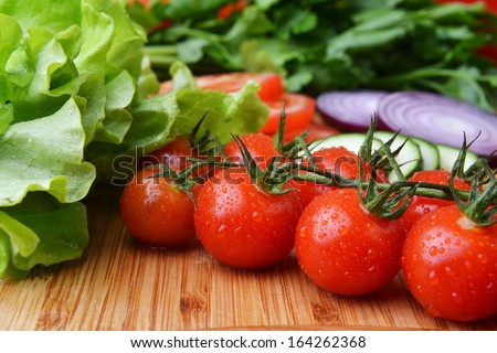 fresh vegetables. Included are tomatoes, cucumber, onions and green leaves - stock photo