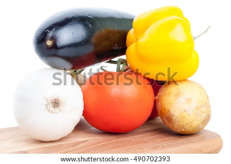 Fresh vegetables ingredient set for vegetarian stew cooking on wooden boat isolated on white background