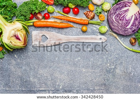 Fresh vegetables ingredients and wooden cooking spoon with heart on gray rustic background, top view.  Vegetarian food, health and diet nutrition concept. - stock photo