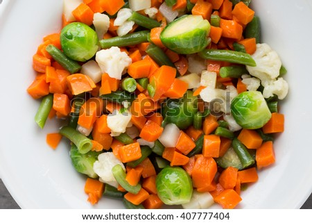 Fresh vegetables mix in a white bowl.