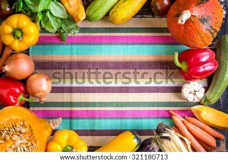 Fresh vegetables on a colorful striped kitchen towel. Autumn background. Healthy eating frame. Sliced pumpkin, bell peppers, carrots, onions, cut garlic, tomatoes, rucola and basil. Top view