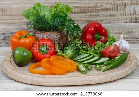 Fresh vegetables on a kitchen board against boards - stock photo
