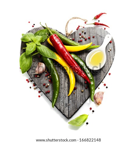 Fresh vegetables on heart shaped cutting board over white (health or vehetarian concept) - stock photo