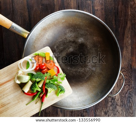 Fresh vegetables on the cutting board are falling in the wok. Concept of cooking. - stock photo