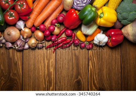 Fresh vegetables on the wooden surface.
