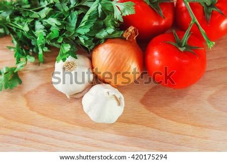 Fresh vegetables on wooden plate - stock photo