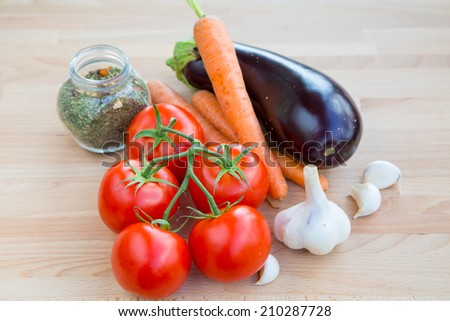 Fresh vegetables organic food set still life with eggplant, carrot, garlic and tomato and herbs - stock photo
