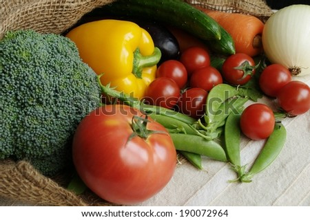 Fresh vegetables pouring out of a brown burlap bag. - stock photo