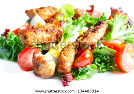 Fresh vegetables salad with fried chicken meat on white plate