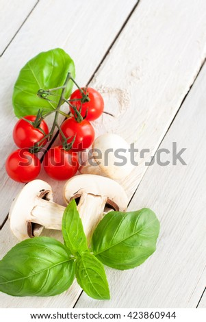 Fresh vegetables - sliced champignons, cherry tomatoes and basil - on wooden background with copyspace, selective focus - stock photo