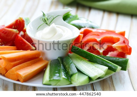 fresh vegetables snack - carrots, sweet pepper, cucumbers and tomatoes with dip - stock photo