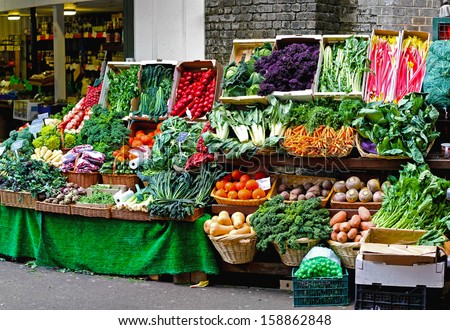Fresh vegetables sold on nicely arranged market stall  - stock photo